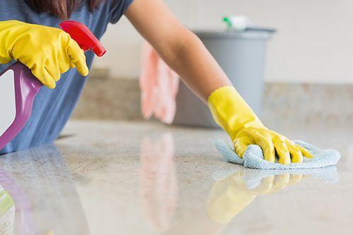 persona limpiando una encimera con guantes puestos y producto limpiador
