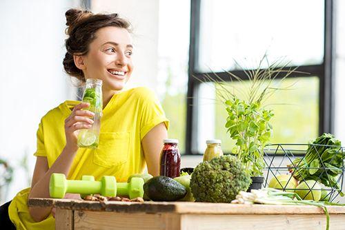 mujer joven bebiendo agua con limón, mesa de madera con unas mancuernas y variedad de verduras