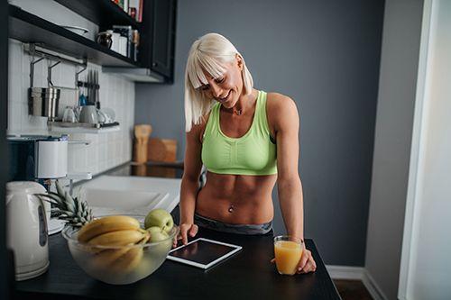 mujer deportista con un vaso de zumo de naranja en la mano, mirando una tablet y un frutero con frutas al lado