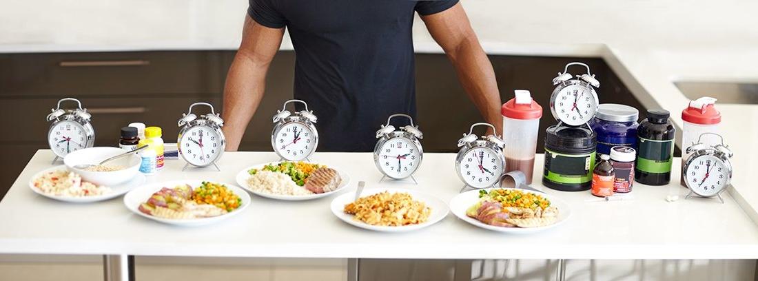 variedad de platos para desyunar con despertadores a los lados y un torso de hombre