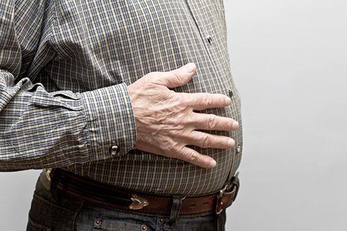 hombre mayor con la mano en el la barriga