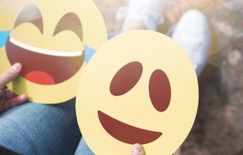 dos emoticonos sonriendo sujetados por unas manos