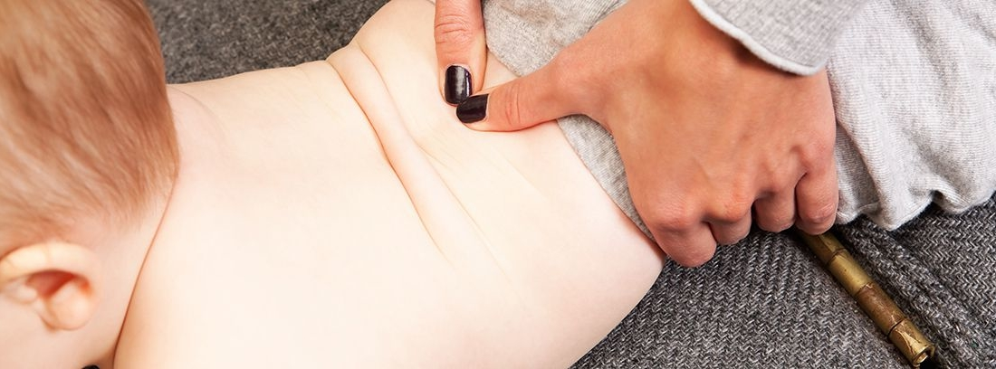 manos masajeando la espalda a un bebé