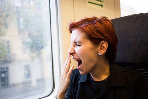 mujer bostezando en el asiento de un tren