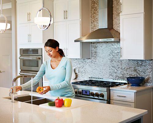 embarazada en el cocina lavando un pimiento