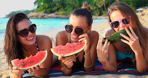 tres chicas en la playa tumbadas comiendo sandia