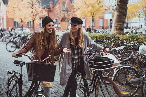 dos chicas con bicicletas sonriendo felices