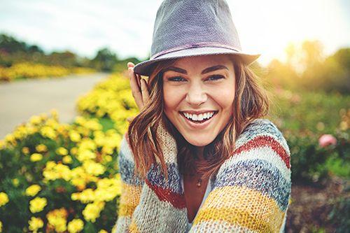mujer en el campo con un sombrero en la cabeza soriendo feliz