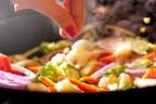 mano condimentando verduras en un wok