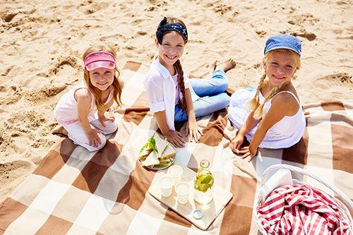 niños haciendo picnic en la playa