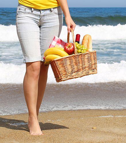 piernas de mujer en la playa con una cesta de comida