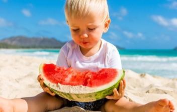 niños rubio en la playa con media sandia en las manos