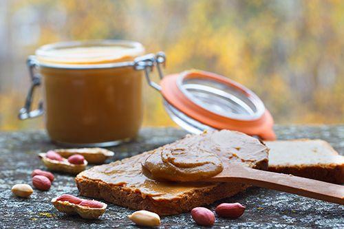 bote de crema de cacahuete con una tostada