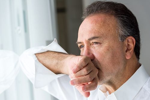 hombre mirando por la ventana con la mano en la boca, con expresión de culpa