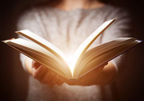 mujer con un libro abierto con luz interior