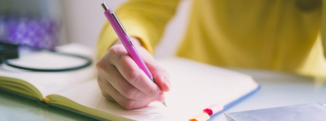mano con un bolígrafo escribiendo en un cuaderno