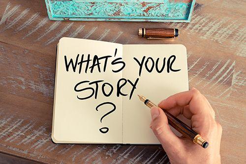 cuaderno con la frase ¿cual es tu historia? y mano con una pluma estilográfica