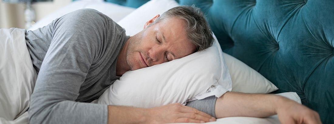 hombre durmiendo de lado con el brazo debajo de la almohada