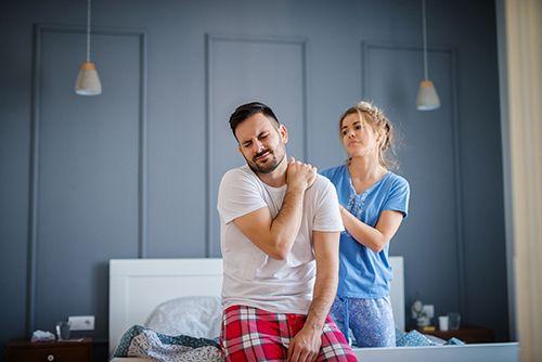 hombre recién despertado con mal dormir y mujer dándole un masaje