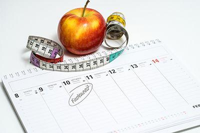 hoja de calendario con una manzana y un metro, ayuno intermitente