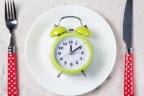 despertador encima de un plato blanco y tenedor y cuchara a los lados con magos de lunares