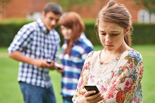 chica mirando el móvil con cara triste y una pareja detrás con móviles en las manos