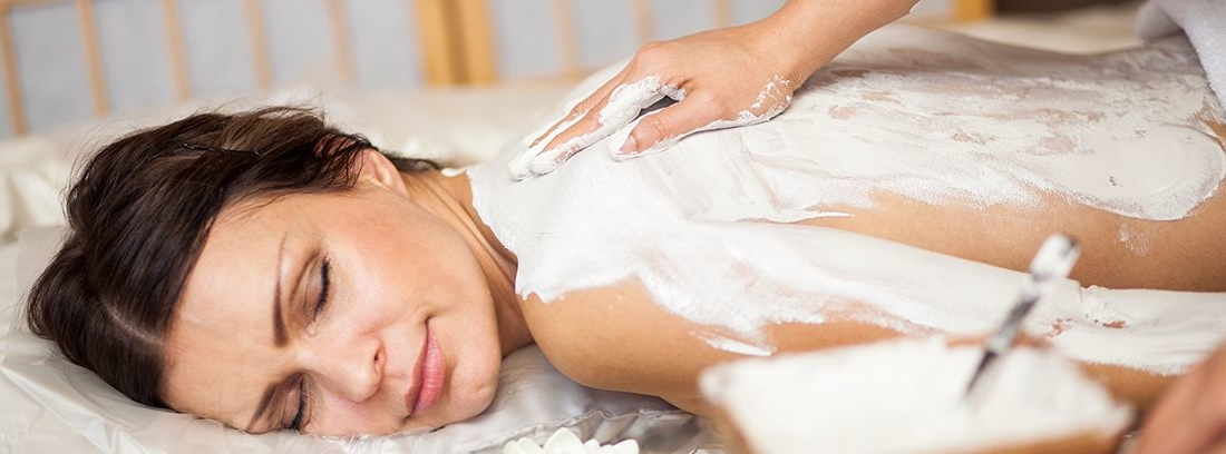 mujer tumbada boca abajo y otra persona dándole crema en la espalda