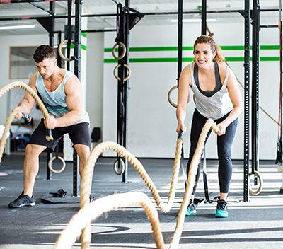 chico y chica en gimnasio realizando ejercicios de fitness con cuerdas