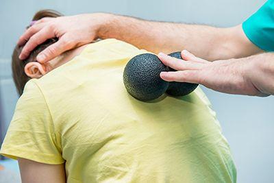 mujer con dos pelotas en las espalda dándose rehabilitación