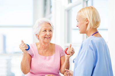médico rehabilitador con paciente con pelotas de distintos colores en las manos