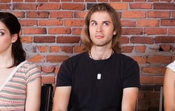 dos chicas y un chico en el medio mirándose de reojo por verguenza