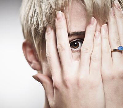 mujer con pelo corto tapándose la cara con las manos, dejando un ojo al descubierto