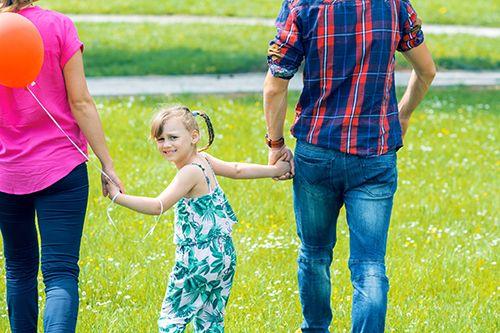 padres e hija paseando por el campo