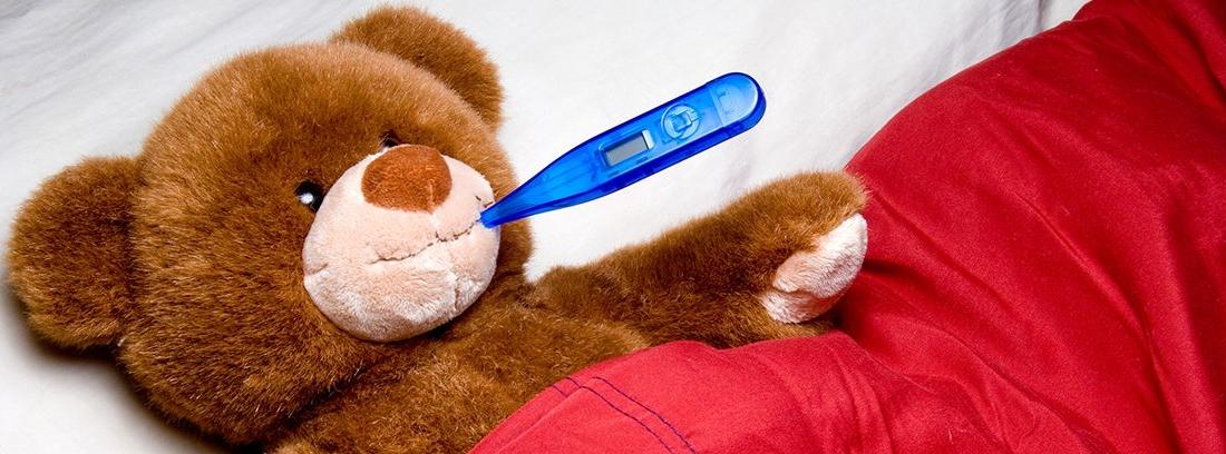 oso de peluche tumbado en la cama con un termómetro azul en la boca