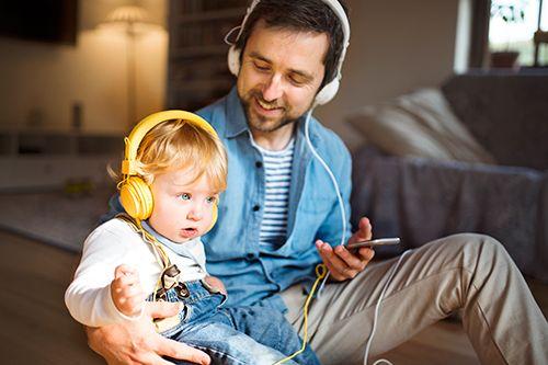hombre y bebé escuchando música con auriculares