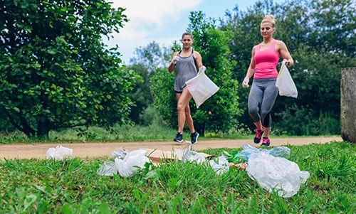 dos chicas corriendo y recogiendo basura
