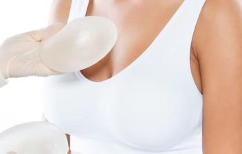 doctor con prótesis en las manos y busto de mujer para realización de mamoplastia