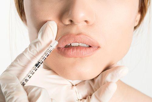 mujer poniendose botox en los labios con una jeringuilla