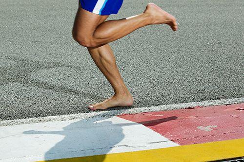 pierna de hombre corriendo descalzo