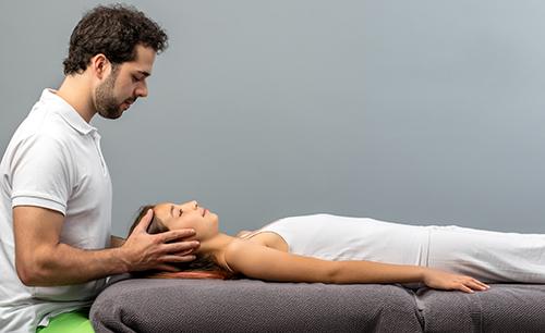 fisioterapeuta dando masajes a una mujer en la cabeza, tumbada en una camilla