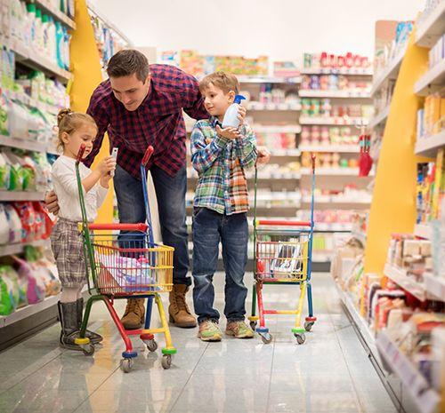 padre haciendo las compra con sus hijos en un supermercado
