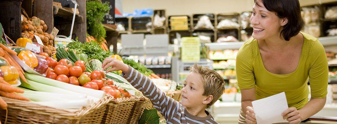 madre con su hijo haciendo la compra en la sección de verduras