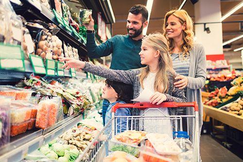 padre y madre realizando la compra con una niñoa y un niño en un supermercado