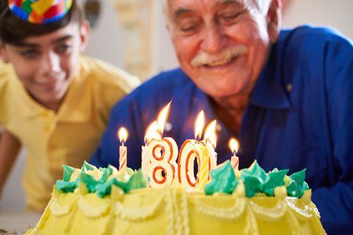 señor mayor soplando las velas de su 80 cumpleaños