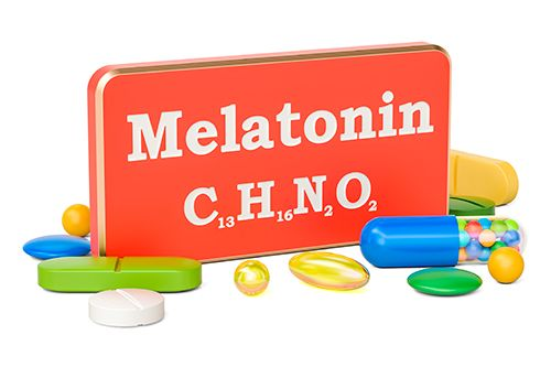 caja de metal roja de melatonina y diferentes pastillas alrededor