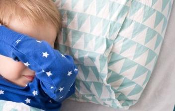 niño acostado con el brazo sobre la cara y un despertados al lado