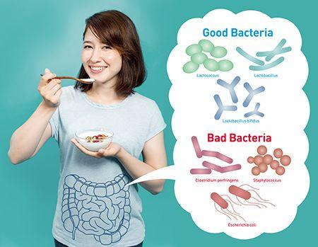 chica comiendo yogur y una nube de bacterias señalando su intestino