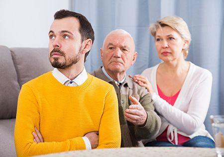 hombre con sueter amarillo, en actitud rencorosa dando la espalda a un hombre y una mujer mayor
