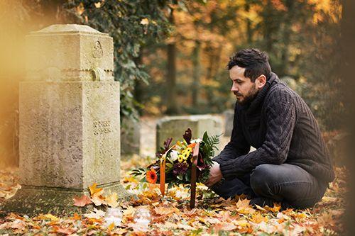 hombre llevando flores a un cementerio