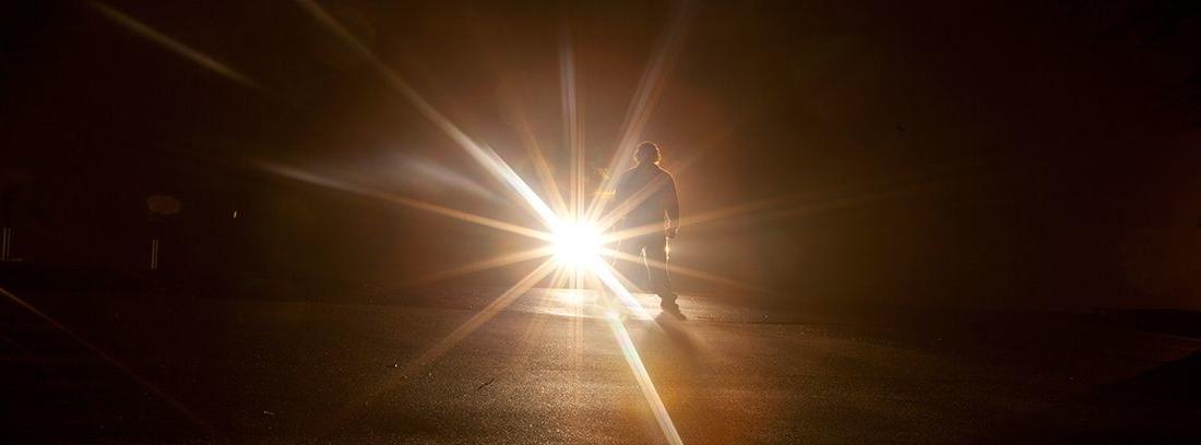 silueta de hombre detrás de una luz brillante